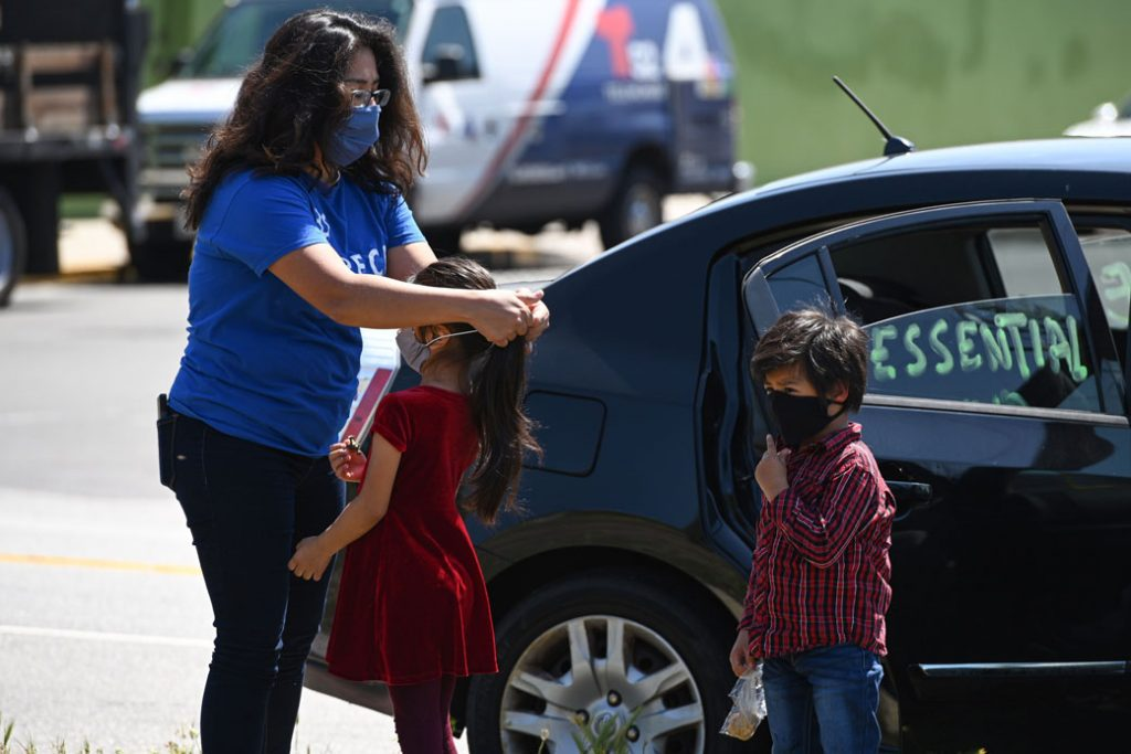 """A mother puts a mask on her children as day laborers and their supporters participate in a """"Caravan for Essential and Excluded Workers"""" in an effort to ensure that COVID-19-related emergency financial aid reaches day laborers, undocumented workers, and their families, Los Angeles, April 2020."""