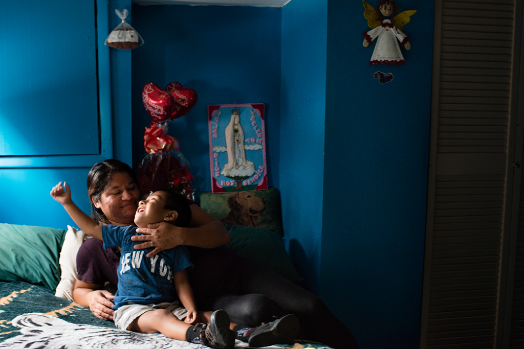 A mother who works for a cleaning company at the Fairmont Hotel and earns the minimum wage is pictured in her Washington apartment with her 2-year-old son, July 2015.