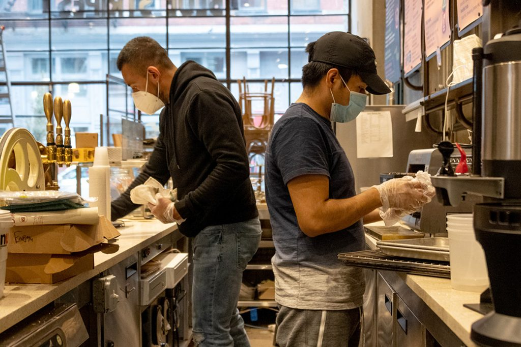 Two employees wearing masks and gloves clean inside a restaurant as it prepares to reopen for takeaway and delivery orders after being closed for more than a month amid the coronavirus pandemic, May 2020, in New York City.