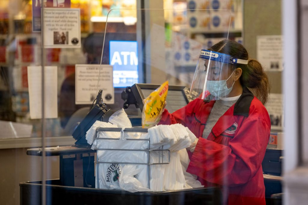A New York City supermarket employee wears a mask, face shield, and gloves as she bags groceries on April 28, 2020.
