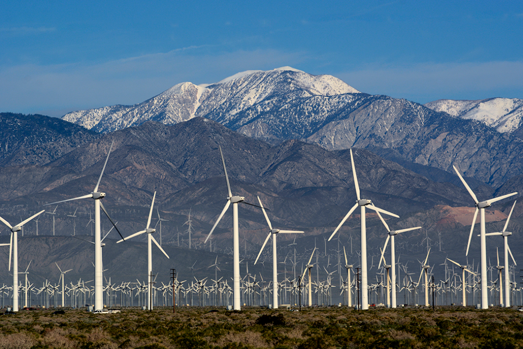 Wind turbines generate electricity near Palm Springs, California, with snow-covered Mt. San Jacinto in the background, February 2019.
