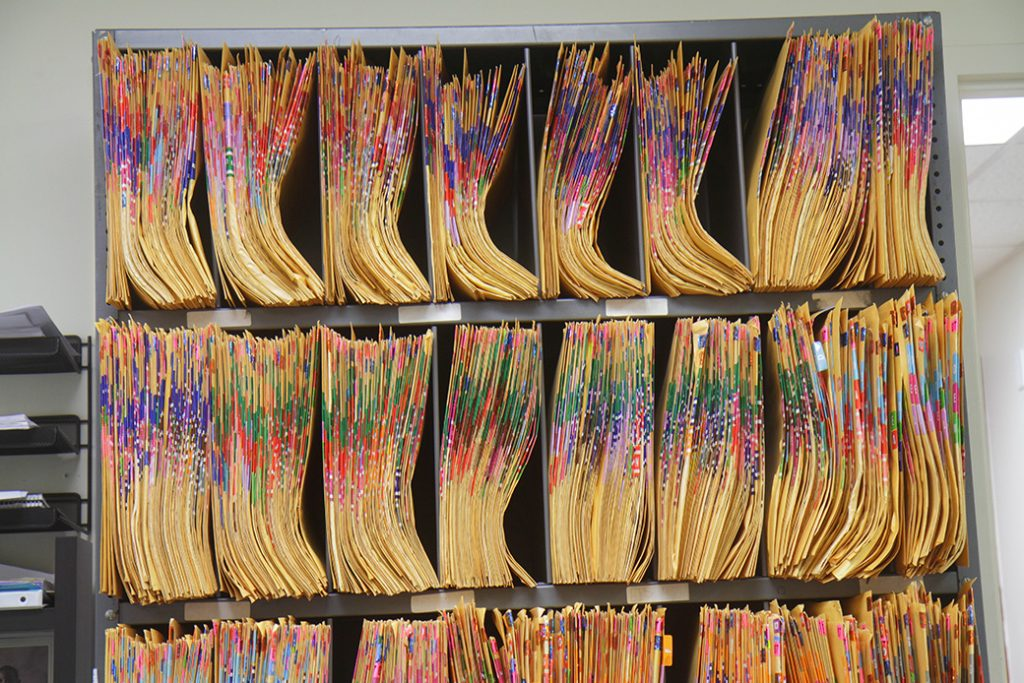 A file cabinet with color coded folders is seen in a doctor's office.