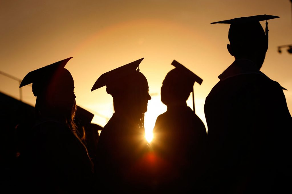 Students line up to receive their diplomas during a graduation ceremony at sunset in Santa Monica, California, June 2013.