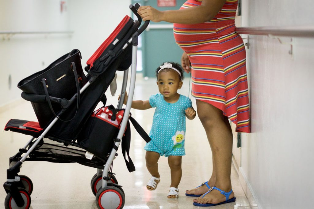 An expectant mom waits in a hallway with her 1-year-old daughter in Loiza, Puerto Rico, on August  30, 2016.