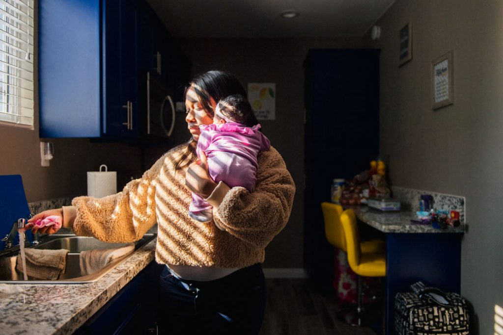 A mother holds her young child as she runs the faucet before a meeting with family over Zoom on November 26, 2020, in Los Angeles.