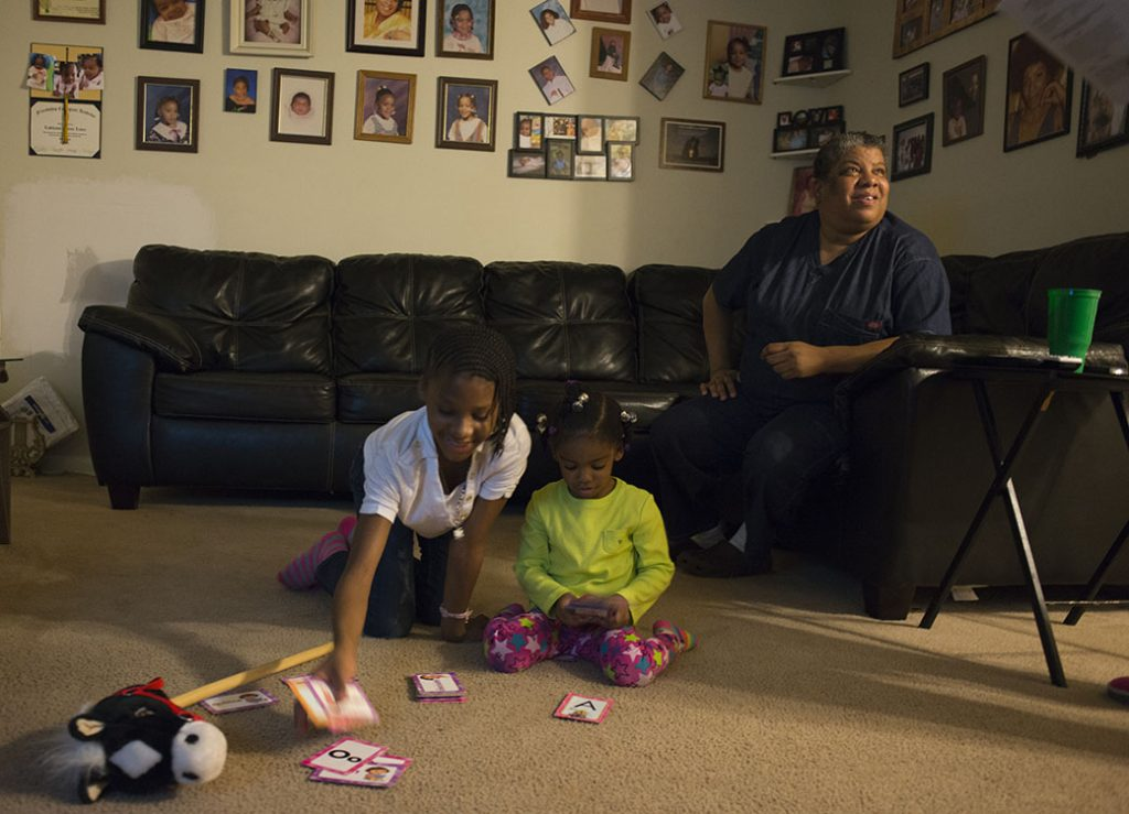 A disabled woman is photographed in her Washington, D.C., apartment, which she can barely afford with public assistance, with family members, October 2012.