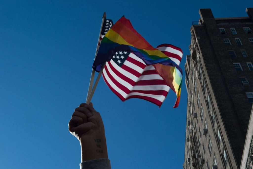 People hold signs and flags in front of the Stonewall Inn in New York during a rally in support of immigrants, asylum-seekers, refugees, and the LGBTQI community, February 2017.