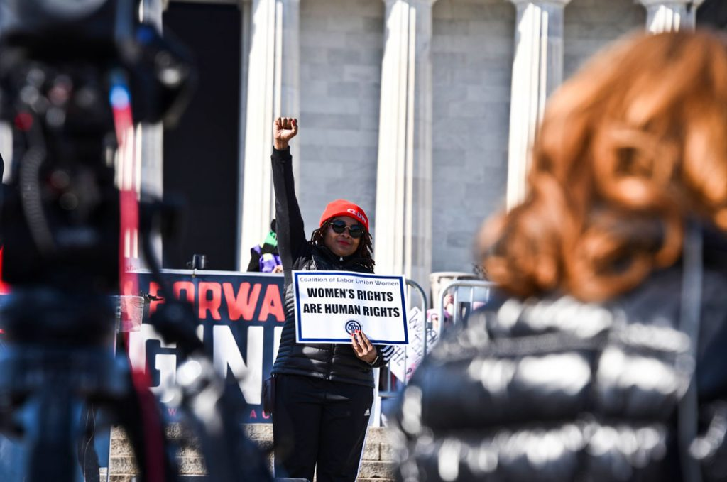 Rachel Bryan of the International Brotherhood of Electrical Workers holds a sign next to the podium in front of the Lincoln Memorial on the anniversary of the Women's March, January 2018.