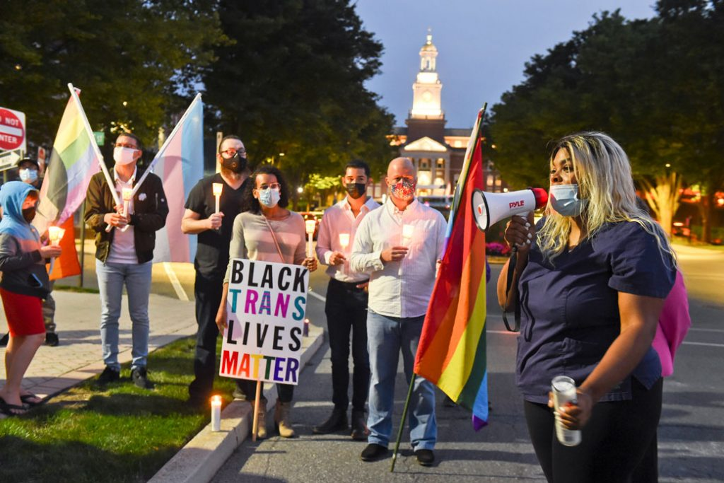 People holding signs supporting Black transgender people gather during a candlelight vigil in West Reading, Pennsylvania, on September 14, 2020.