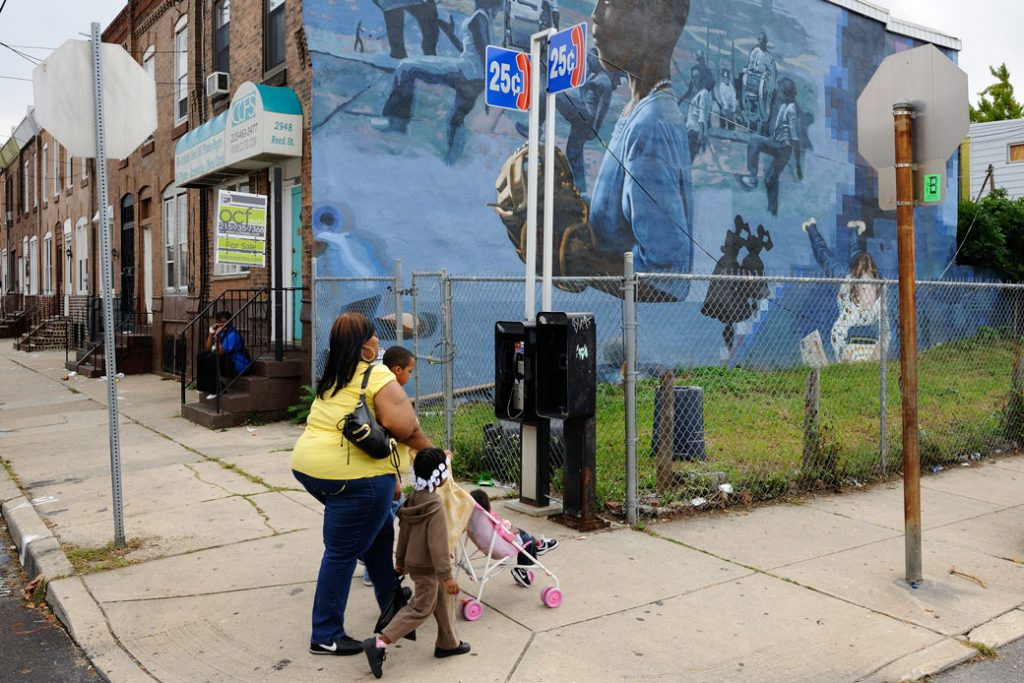A family walks through a Philadelphia neighborhood on September 17, 2013.