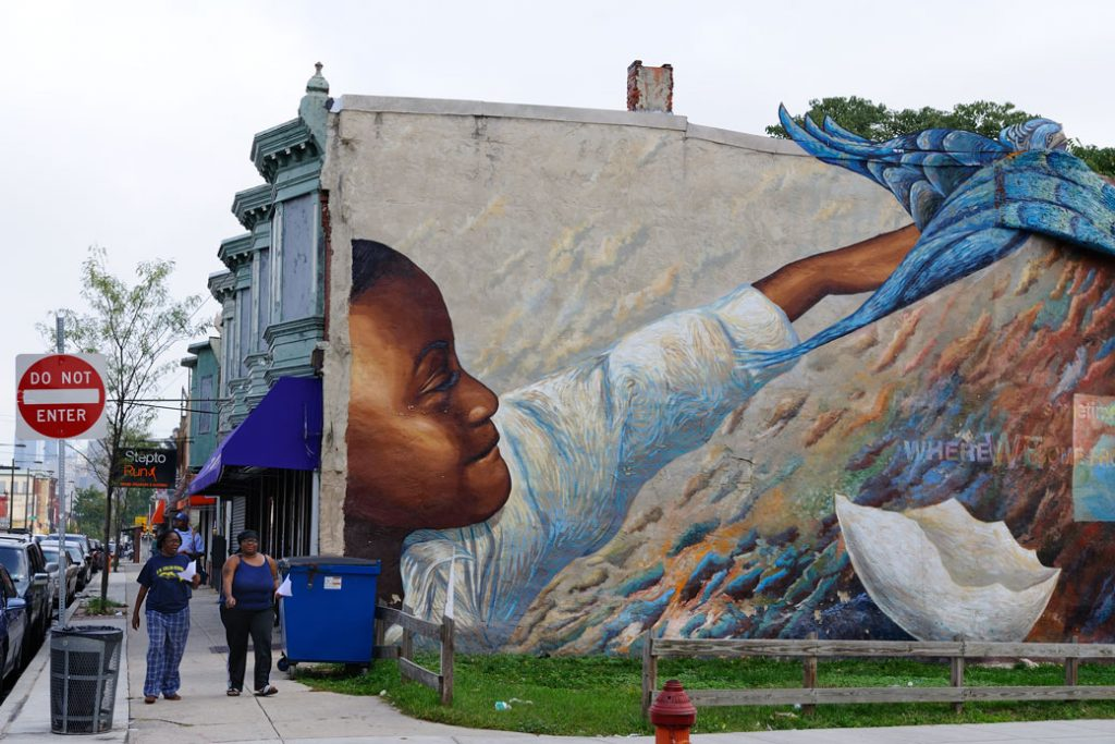 "A group of people walk past the ""Dream in Flight"" mural in Philadelphia—part of the city's Mural Art Program—on September 17, 2013."