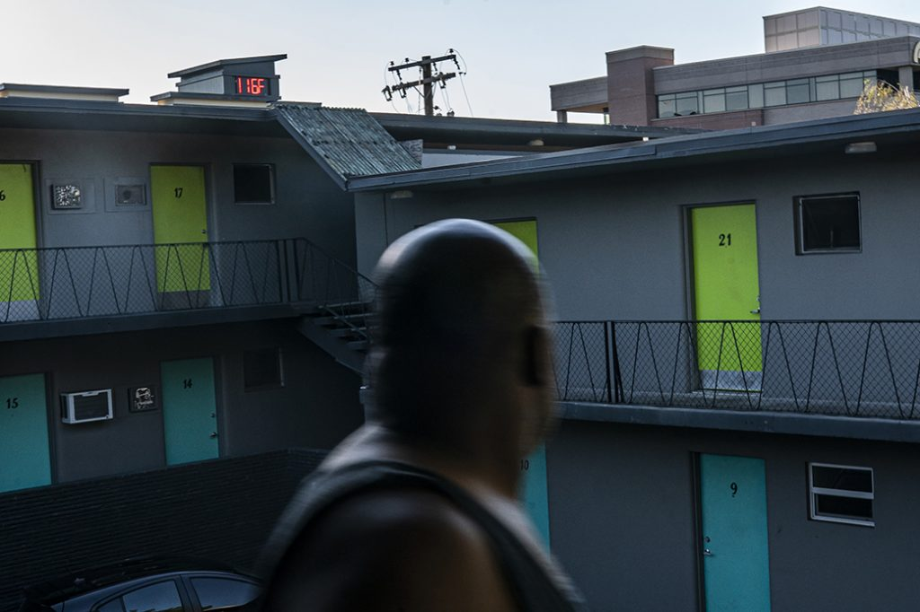 A man looks at a digital thermometer on a nearby building that reads 116 degrees Fahrenheit while walking to his apartment, June 2021, in Washington state.