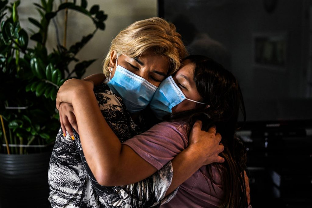 A mother embraces her daughter inside their home in Miami Gardens, Florida, on August 11, 2020.