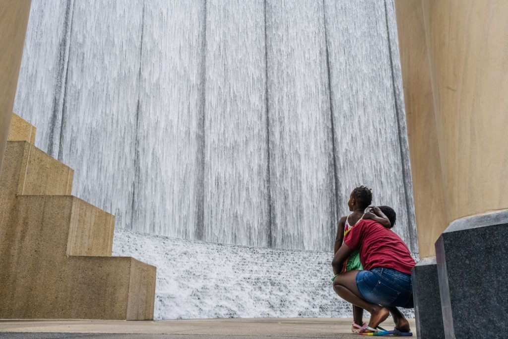 A woman and child visit Houston's Gerald D. Hines Waterwall Park on August 3, 2021.