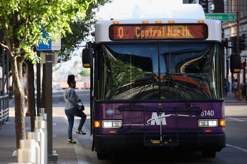 A woman steps onto a bus in Downtown Phoenix on March 26, 2020.