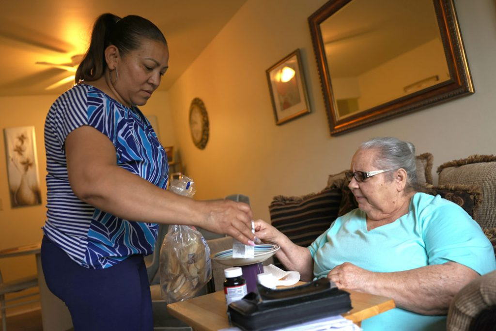 A home health aide in Haverstraw, New York, gives a patient her medicine on May 5, 2021.