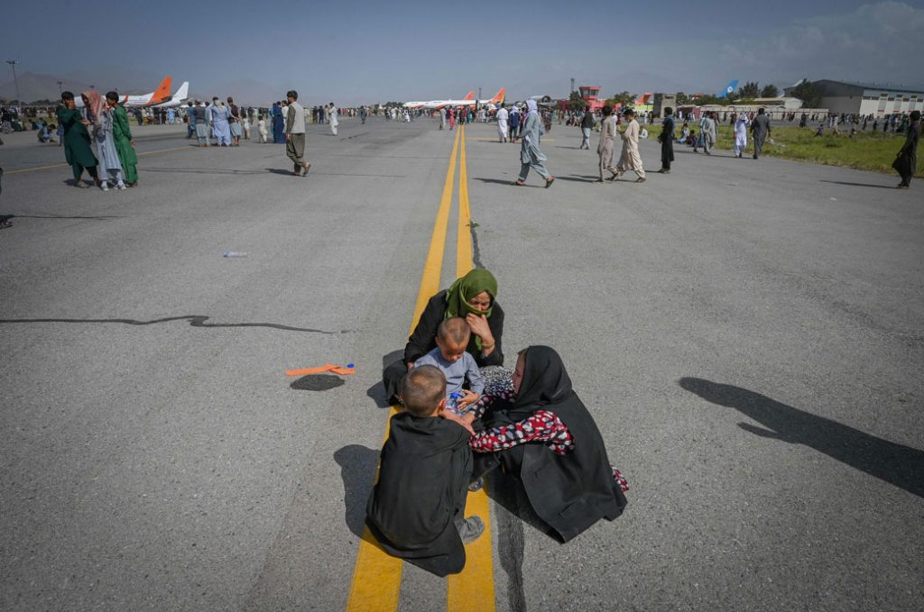 Afghan people sit along the tarmac as they wait to leave the Kabul airport in Kabul, August 2021.