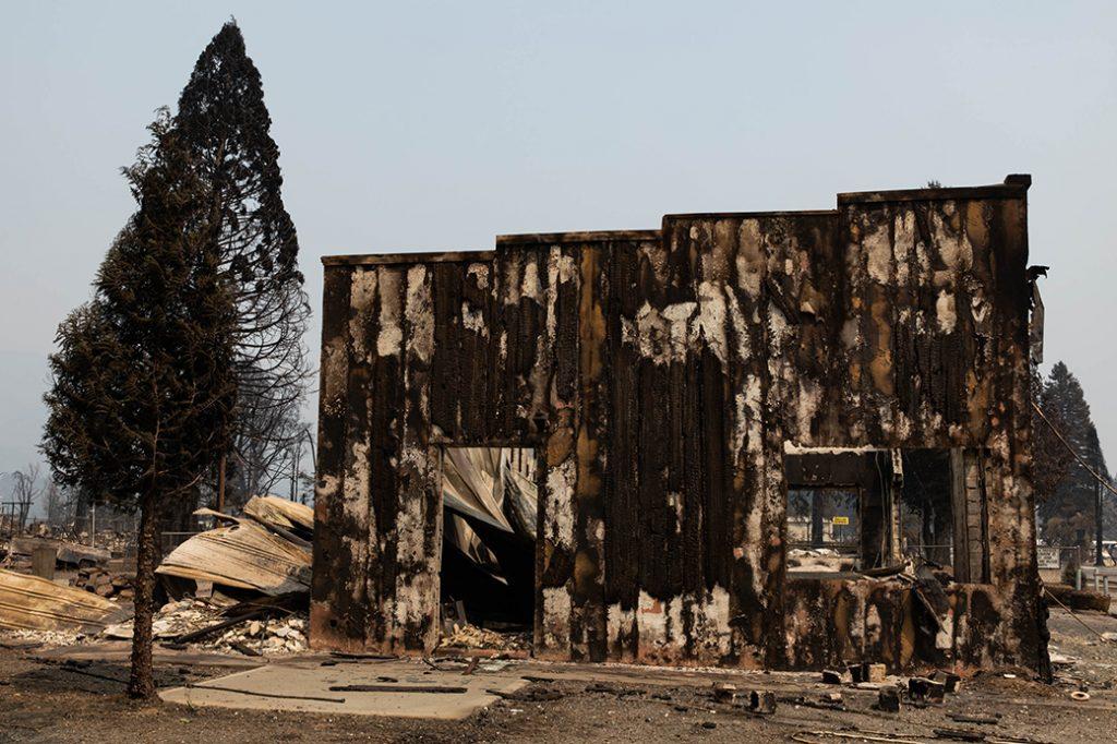 A building that burned in the Dixie Fire remains standing amid rubble on August 8, 2021, in Greenville, California.