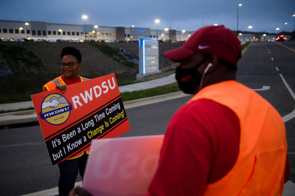 Union organizers wave to cars exiting an Amazon fulfillment center on March 27, 2021, in Bessemer, Alabama.