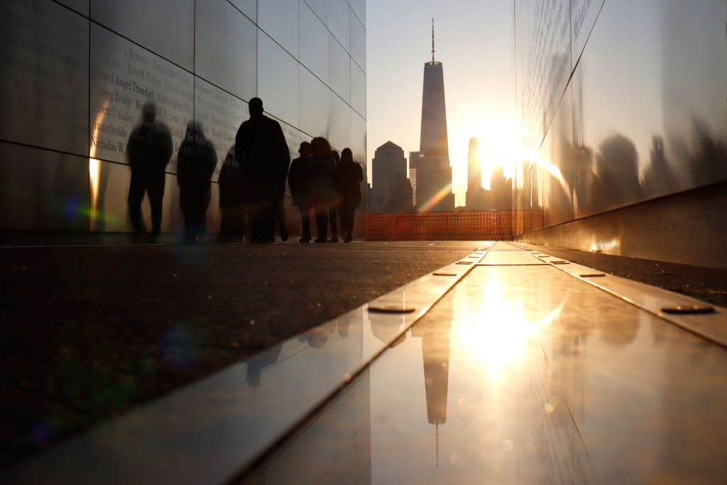 The sun rises behind the skyline of lower Manhattan and One World Trade Center in New York City as people walk through the Empty Sky 9/11 memorial in Jersey City, New Jersey, on April 24, 2021.