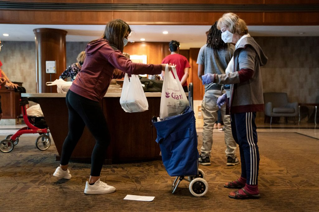 A volunteer does no-contact delivery for seniors at a residential complex in North Bethesda, Maryland, April 2020.