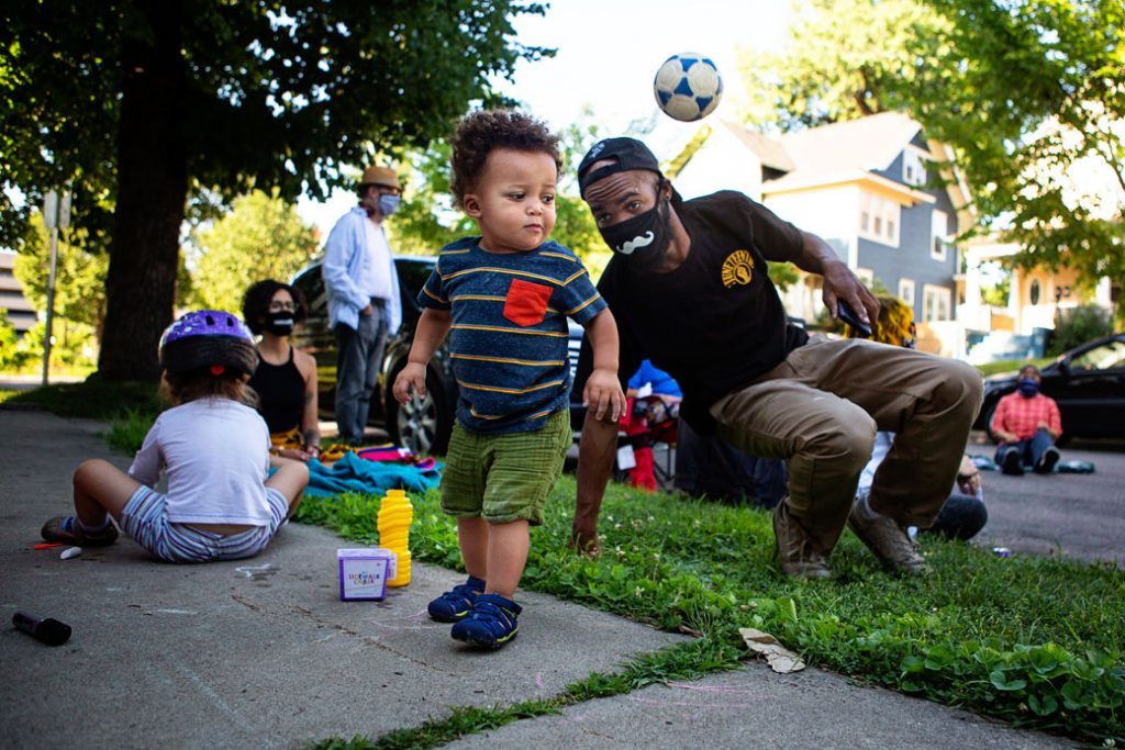 A toddler bounces a ball as his father keeps watch during a community conversation in Minneapolis, July 2020.