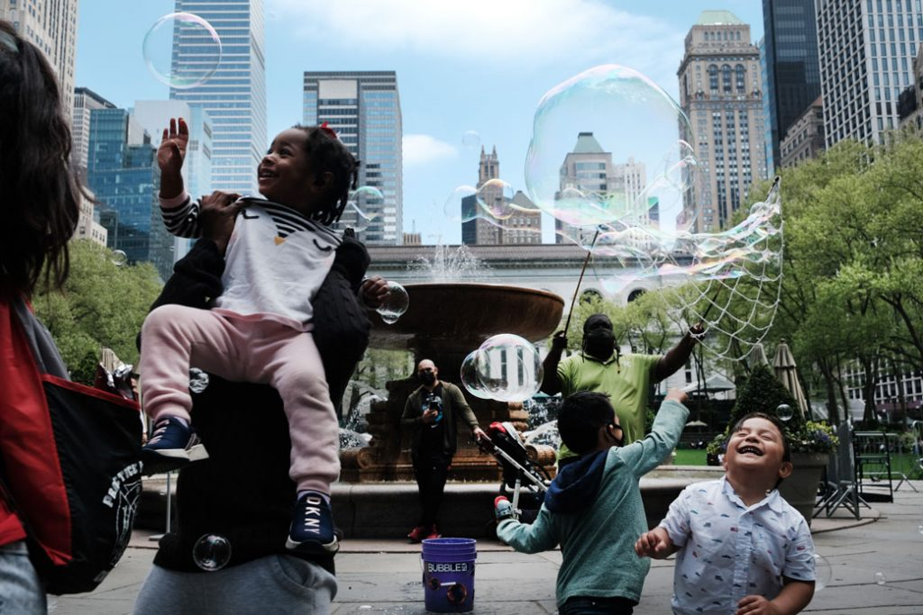 Children and adults play with bubbles at Bryant Park in Manhattan, New York, on May 4, 2021.