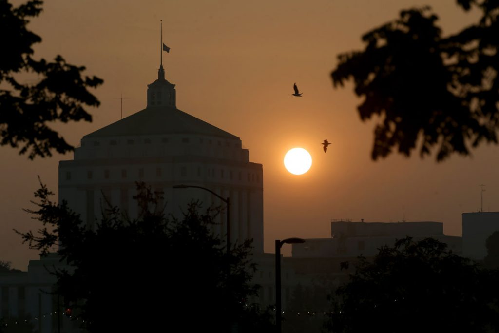 A smoky sunset is seen behind the Alameda County Superior Courthouse in Oakland, California, on September 14, 2020.