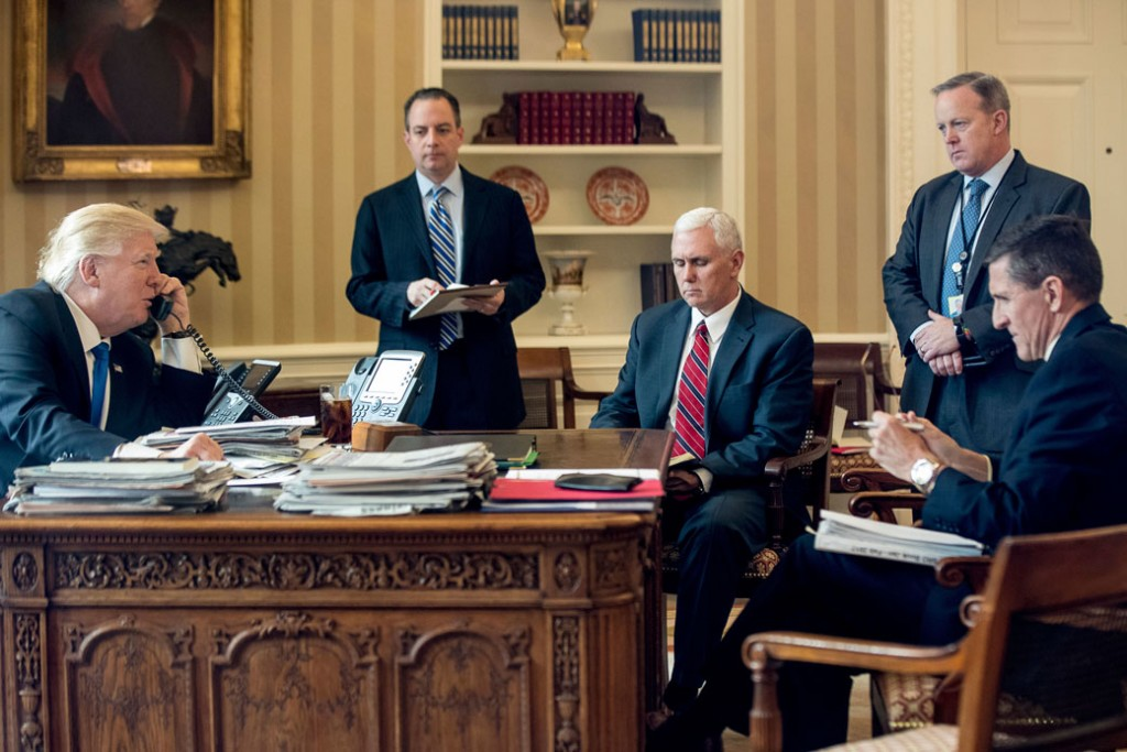 President Donald Trump—accompanied by, from the left, Chief of Staff Reince Priebus, Vice President Mike Pence, White House press secretary Sean Spicer, and National Security Adviser Michael Flynn—speaks on the phone with Russian President Vladimir Putin on January 28, 2017, in the Oval Office.