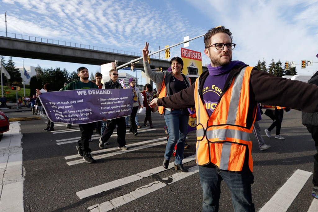 A labor union staffer holds back traffic during a march by demonstrators near Seattle-Tacoma International Airport, November 2016.