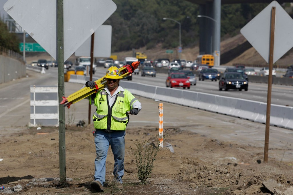 A construction worker carries survey equipment along the 405 Freeway near the Brentwood section of Los Angeles, October 2010.