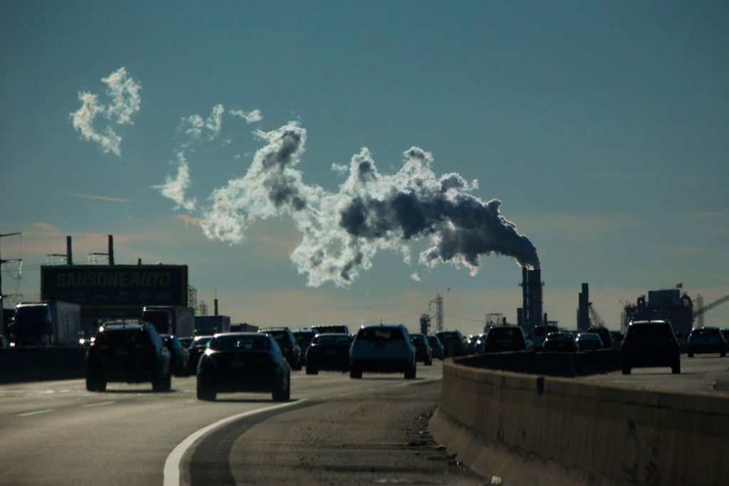 Vehicles move along the the New Jersey Turnpike while a factory emits smoke in Carteret, New Jersey, November 2017.