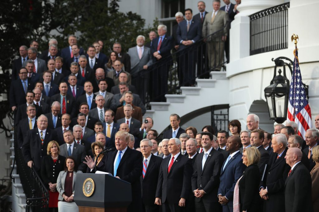President Donald Trump, flanked by Republican lawmakers, celebrates Congress passing the Tax Cuts and Jobs Act on the South Lawn of the White House on December 20, 2017.