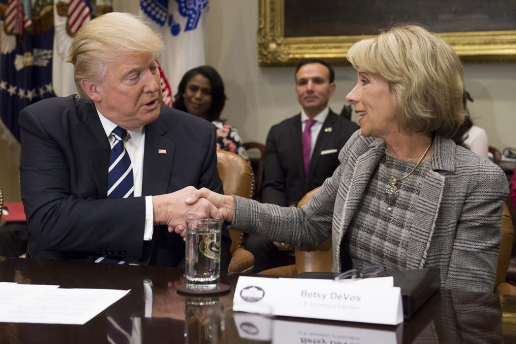 Education Secretary Betsy DeVos shakes hands with President Donald Trump during a White House meeting, February 2017.