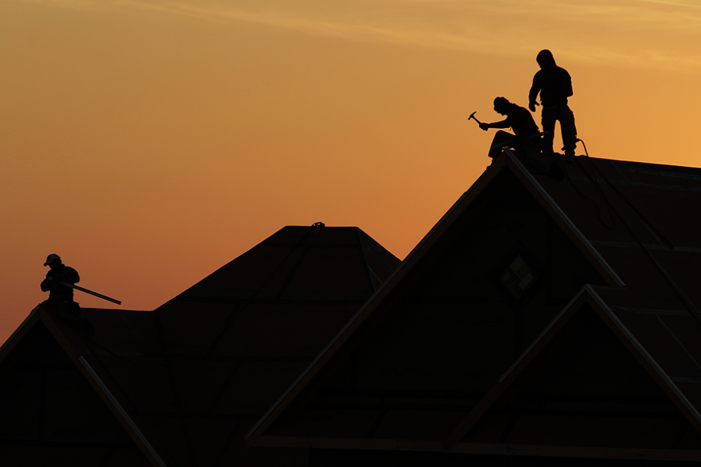 Workers are silhouetted as they build a home in Joplin, Missouri, January 19, 2012.