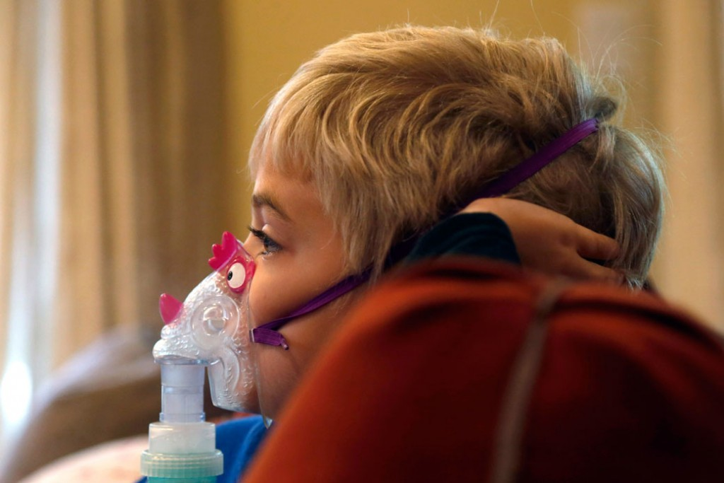 Carter Howard watches a cartoon during his asthma treatment in Northbrook, Illinois, on October 15, 2013.