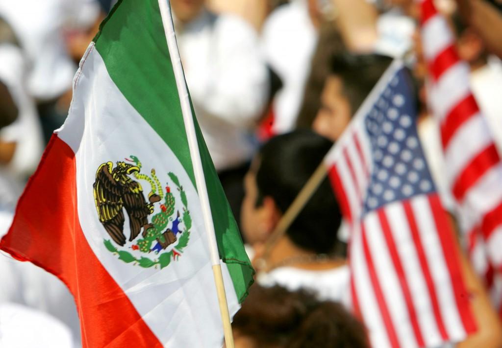 Las banderas mexicanas y estadounidenses son llevadas en el Capitolio estatal en Little Rock, Ark., lunes 10 de abril de 2006, por manifestantes en un mitin organizado por la Coalition for Comprehensive Immigration Reform de Arkansas.