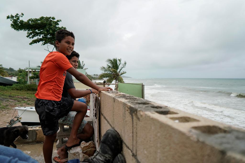 Jóvenes miran hacia el mar mientras la tormenta tropical Karen se acerca a Yabucoa, Puerto Rico, septiembre de 2019.