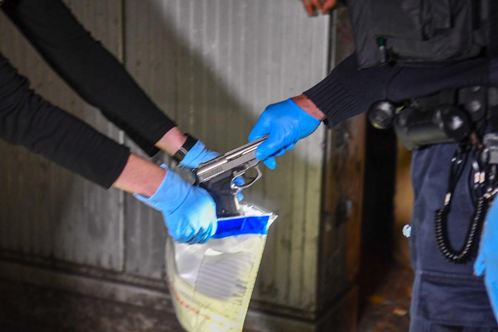 Los policías colocan un arma en una bolsa de pruebas, agosto de 2019.