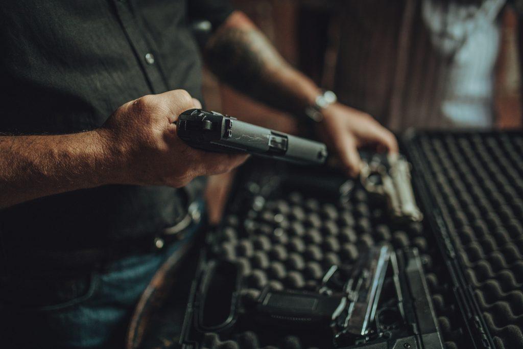 Dos hombres, delincuentes que venden armas en el mercado negro de una casa abandonada.