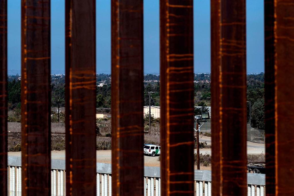 Un vehículo de patrulla fronteriza se puede ver a través de una sección reforzada de la valla fronteriza entre Estados Unidos y México desde Tijuana, México.