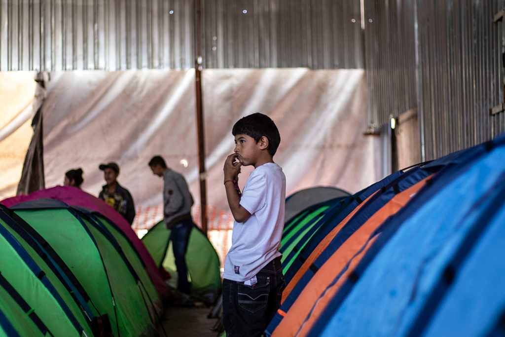 Un niño migrante mexicano es fotografiado junto a tiendas de campaña en un refugio en Tijuana, México, cerca de la frontera con Estados Unidos, octubre de 2018.
