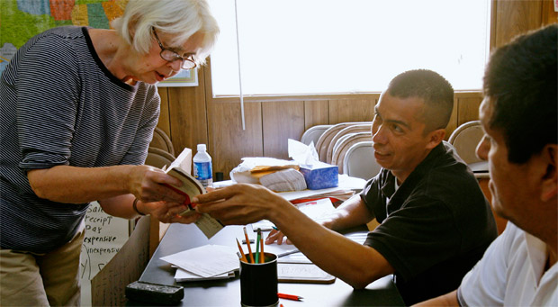 Marcia Roop, left, teaches an English lesson to David Perdomo, of Vienna, Virginia, and Jose Martinez, of Reston, Virginia, at the Herndon Official Workers Center in Herndon, Virginia.