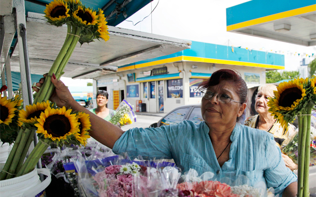 Margarita Briones selects bouquets of flowers for her customers at her flower shop Margarita Flowers, Friday, July 6, 2012, in Miami.