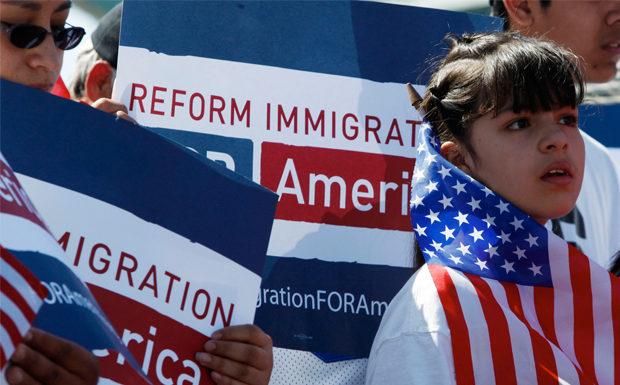 An unidentified woman waves an American flag while attending a rally to spur lawmakers to consider reform on immigration policies in Confluence Park in Denver on Sunday, March 21, 2010.
