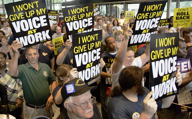 Supporters attending a labor rally hold signs supporting rights to unionize at the United Steelworkers union headquarters in Pittsburgh.