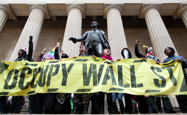 Occupy Wall Street demonstrators stand and cheer in front of the George Washington statue on Wall Street.