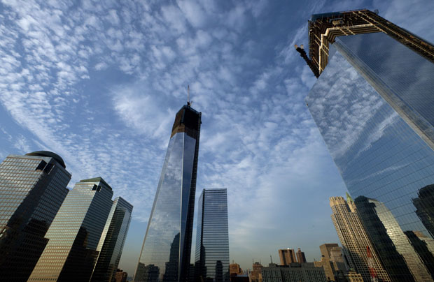 One World Trade Center, center, rises above the National September 11 Memorial and Museum at the World Trade Center, Thursday, September 6, 2012, in New York.