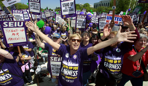 In this May 20, 2011, file photo taken in Salem, Oregon, Cathy Williams, center, of Portland, stands with thousands of state workers gathered at the Oregon Capitol. Oregon is one of the top states in the country when it comes to union membership, with more people joining unions there each year.