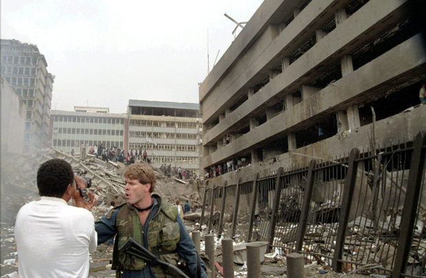 A security guard instructs a cameraman to move back following a bombing that heavily damaged the U.S. Embassy in Nairobi, Kenya, right, Friday, August 7, 1998. Nine Americans serving in the embassy were killed in the bombing, including Deputy Chief of Mission Julian Bartley.